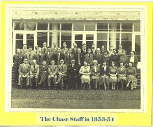 Photograph of the Chase staff 1953 -4, in front of the main entrance. The headteacher, Mr Garth is sat in the centre