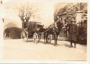 A railway cabman at work with his horse drawn cab outside Portland House, Great Malvern
